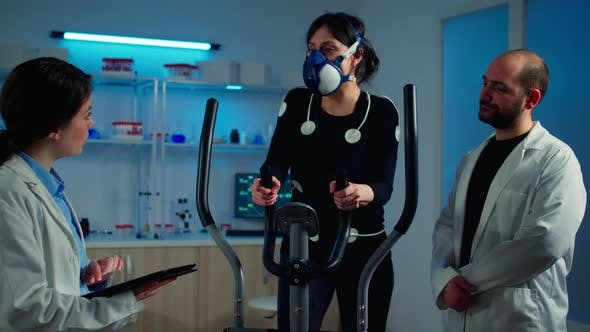 Woman Athlete with Mask Doing Fitness Exercises in Science Sport Lab