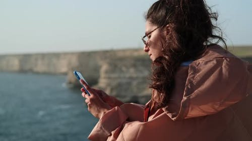 Wistful Woman with Phone By the Sea