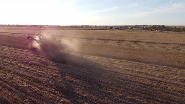 Thumbnail for Luftaufnahme eines funktionierenden Traktors mit einem Pflug in einem Feld eine staubige landwirtschaftliche Maschine für die Ernte