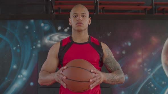 Thumbnail for Ernsthafter Backetball-Spieler, der Basketball hält