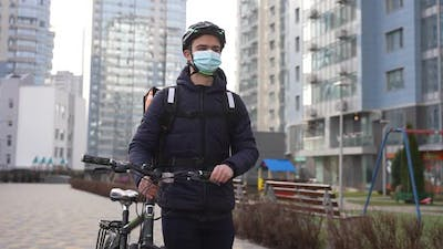 Masked Delivery Food Courier Walking Carrying Bike