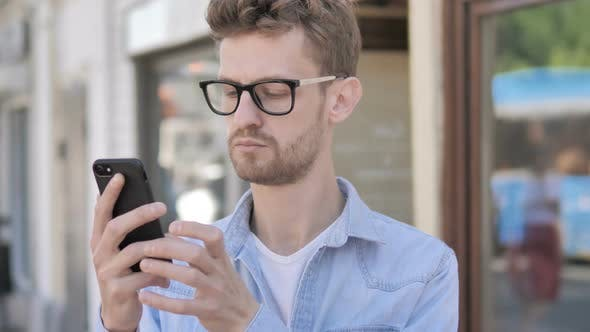 Thumbnail for Casual Young Man Using Smartphone while Standing Outdoor