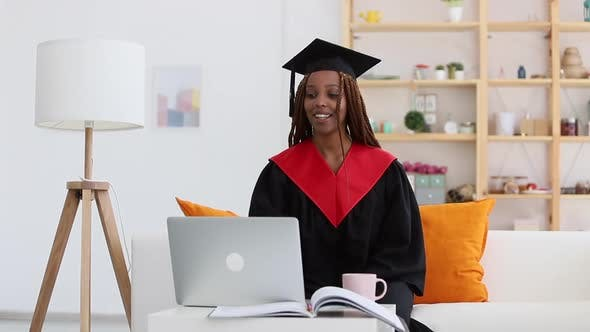 Black Woman in Cap and Gown Waving Greeting Person in Video Call Spbi