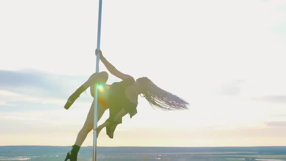 Cover Image for Pole Dance on Nature - Sexy Attractive Woman with Long Blue Braids in Black Dress Dancing on the