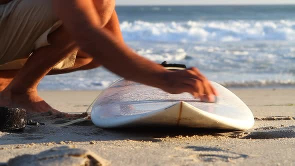 Thumbnail for A surfer waxing board before surfing