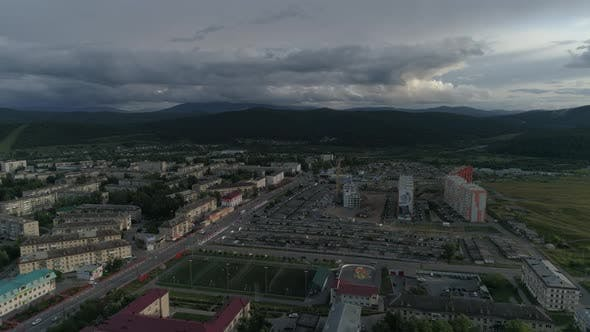 Thumbnail for Aerial view of city with hight and low buildings. Outside the city Ural mountains.