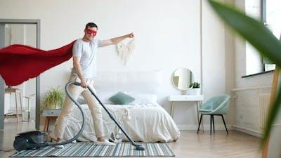 Portrait of Smiling Superman Vacuuming Carpet at Home and Looking at Camera