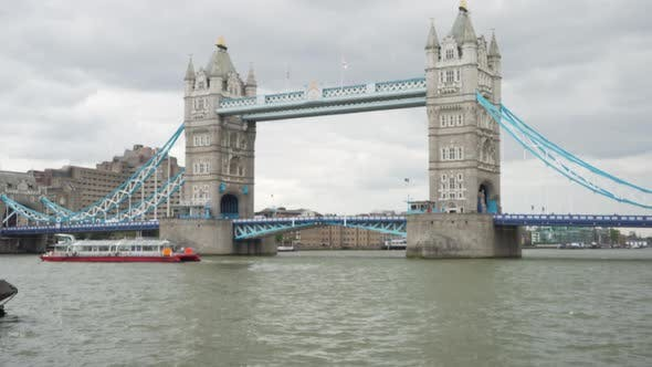 Out of focus shot of iconic Tower Bridge in London, boat floating on river