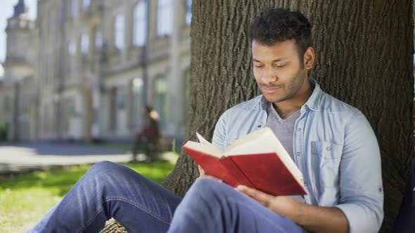 Thumbnail for Male Reading Favorite Novel Under Tree Pressing Book Against Chest Daydreaming
