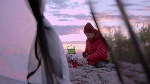Mann macht Kaffee beim Camping bei Sonnenuntergang