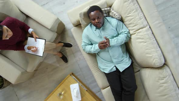 Thumbnail for Top View of Black Man Lying on Sofa and Talking with Female Counselor