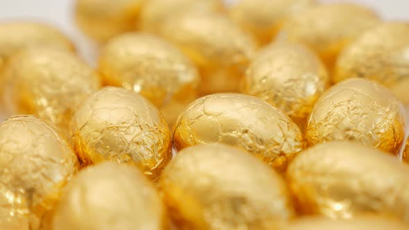 Thumbnail for Chocolate Easter golden eggs on white surface slow panning 4K 2160p UltraHD footage - Slow pan over