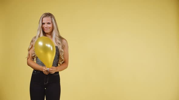Cover Image for Female Model in Silver Tank Top Holding a Ballon Against a Yellow Background