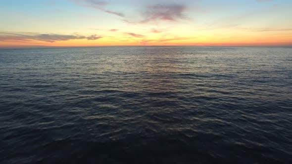 Thumbnail for Aerial shot of the sun setting over the ocean horizon.