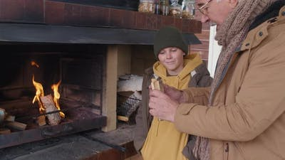 Grandfather and Kid Kindling a Fireplace