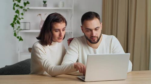Caucasian Couple 30s Years Old Wife and Bearded Husband in Living Room Using Laptop Enjoy Eshopping