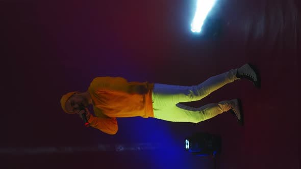 Thumbnail for Vertical Video. Funny Male Rap Artist Sings and Dances Into a Microphone on a Stand in the Neon