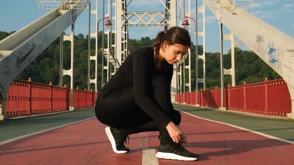Thumbnail for Attractive Woman Tying Shoelace on Sneakers on City Bridge and Starting To Run. Female Athlete Ties