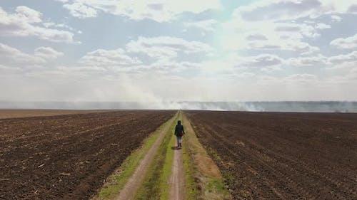 Ein Mädchen geht entlang der Straße im Feld zu dem Ort, wo es ein Feuer