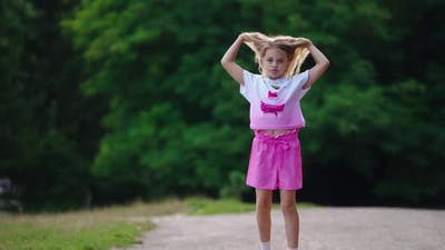 Girl having fun outdoors. View of happy little girl jumping and having fun in park