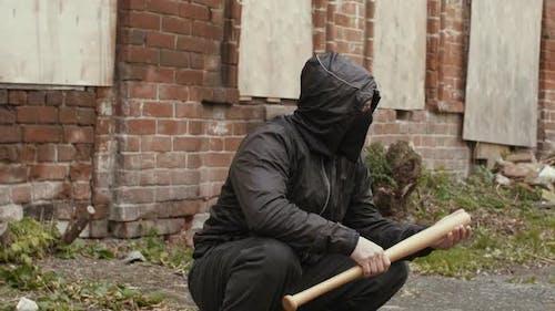 Bandit Mann in schwarzer Maske und Jacke mit Kapuze mit Baseballschläger sitzt auf der Straße