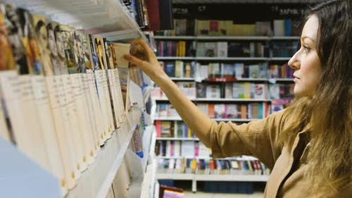 A Young Girl Chooses a Book in a Bookstore