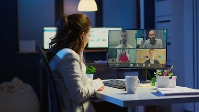 Employee Discussing with Partners Online Using Webcam at Night