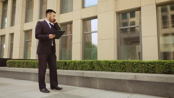 Thumbnail for Very Angry Businessman Walks Down the Street with a Tablet and Talking on the Mobile Phone