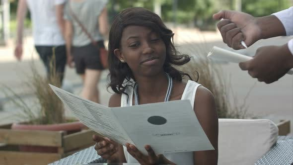 Thumbnail for Attraktive atemberaubende junge Afro American Lady sitzt allein am Cafe Tisch, bereit zu bestellen