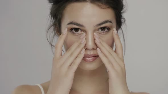Thumbnail for Pretty Woman with Big Dark Eyes and Perfect Skin Moisturizing Her Face with Both Arms