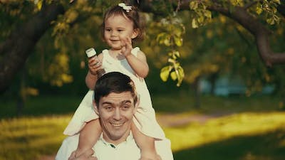 Little Girl Sitting on Daddy's Shoulders