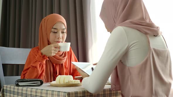 Thumbnail for Young Asian Muslim Women Enjoying A Relaxing Moment in the Coffeeshop