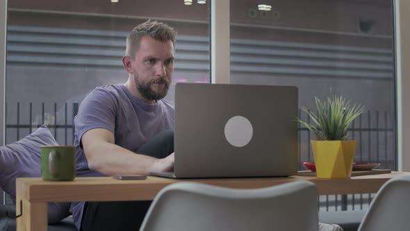 Man with a Beard Uses a Laptop