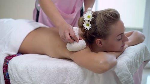 Massage Therapist Using Herbal Compress on Woman