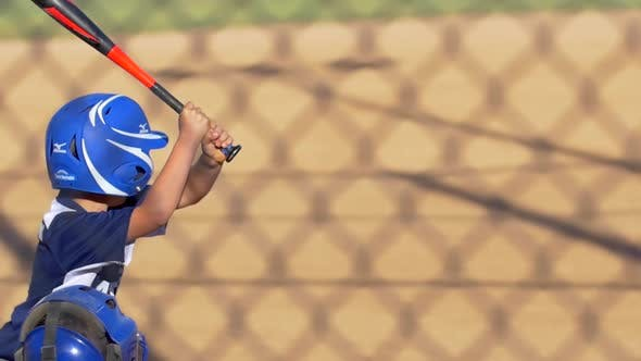 A batter is at bat while playing in a boys little league baseball game.