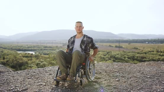 Thumbnail for 30-Aged Disabled Man in Wheelchair Looking at Camera on the Mount