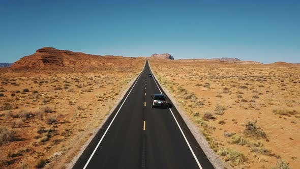 Thumbnail for Drone Follows Two Cars Driving Along Beautiful Highway Road Monuments Valley, Wide Open Endless Dry
