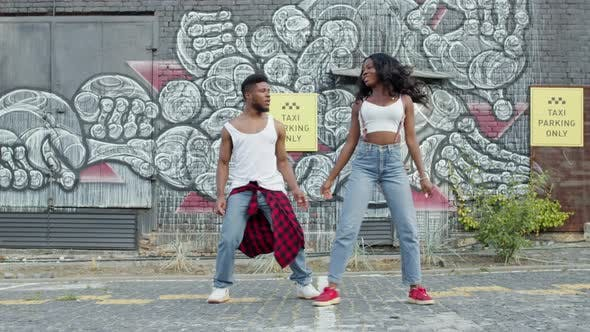 Thumbnail for Black Guy And Girl Dancing On The Street. They Are On Graffiti Wall Background.