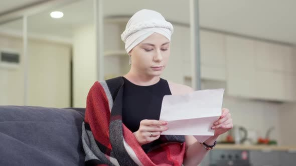 Stressed Upset Young Woman Reading Letter with Bad News Touching Head and Sighing