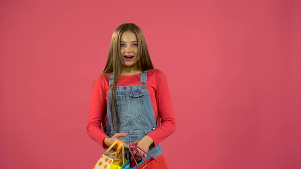 Thumbnail for Girl Gets a Red Shoe From the Bag and Is Happy, Pink Background