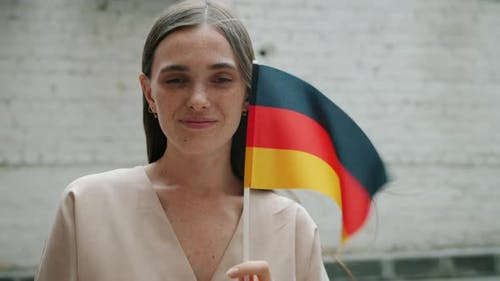 Portrait of Cheerful Woman Holding Official German Flag Looking at Camera Standing Against Brick