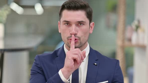 Thumbnail for Serious Young Businessman Putting Finger on Lips