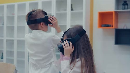 Little Boy and Little Girl in Virtual Reality Headset Standing in Classroom and Looking