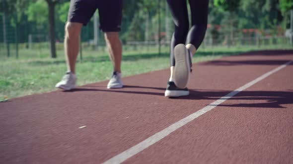 Thumbnail for Legs of Unrecognizable Fit Man and Woman Running on Sunny Track Outdoors. Sportive Caucasian Couple