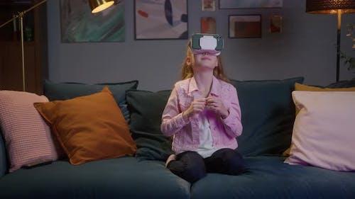 Intelligentes kleines Mädchen mit Virtual Reality Headset verwendet Handgesten, um Augmented Reality zu steuern