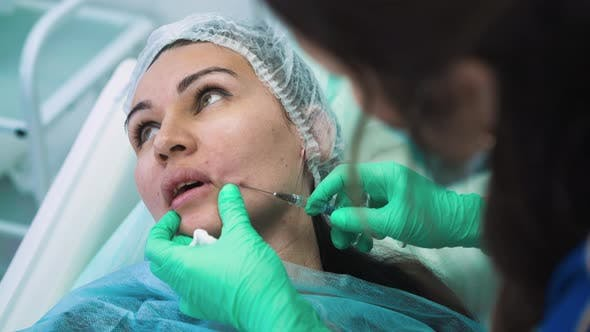 Woman Inserts Needle Under Client Skin for Filler Injection