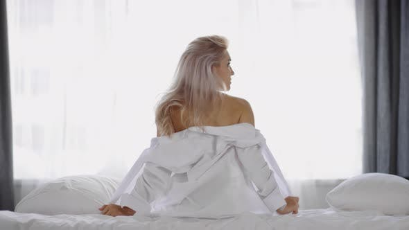 Thumbnail for Back of Woman Sitting on Bed and Taking off White Shirt
