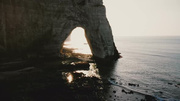 Thumbnail for Drone Flying Along Epic White Cliffs of Normandy Shore Towards Natural Backlit Rock Arch
