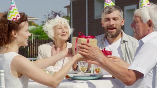Family Congratulating Grandfather on Outdoor Birthday Party