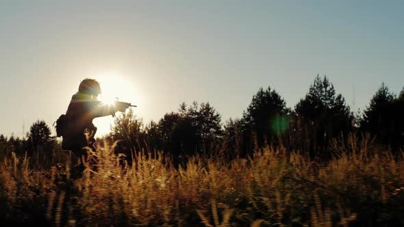 Thumbnail for Silhouette of Armed Men in the Attack. Runs with Arms in the Sun